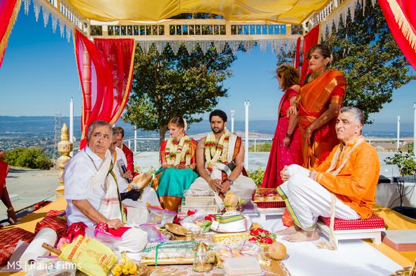 Indian couple sitting under their wedding mandap