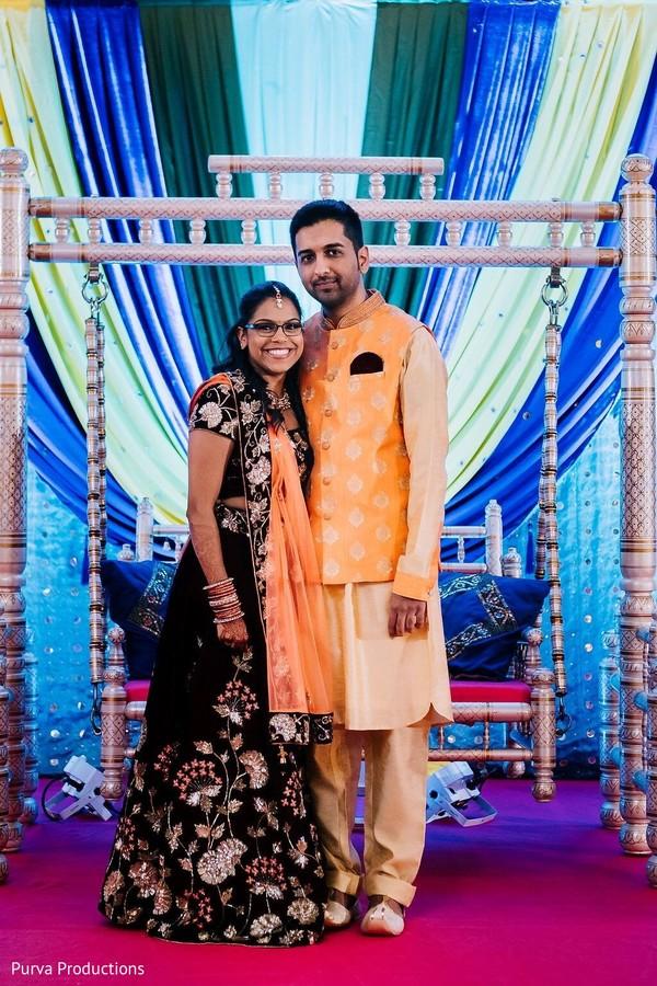 Joyful Indian couple posing at sangeet stage.