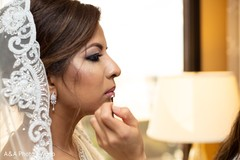 Indian bride being assisted by makeup artist