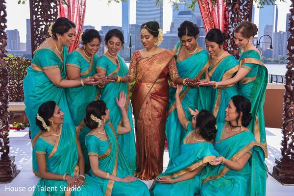 Indian bridesmaids admiring maharani's mehndi art.