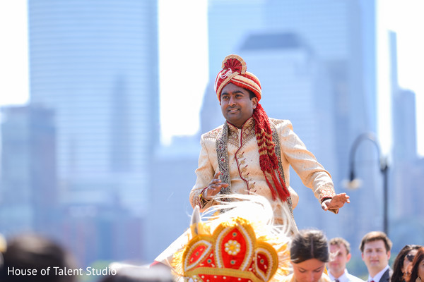 Indian groom riding baraat white horse.