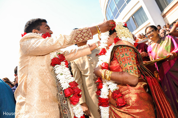 Indian groom putting garland to bride.