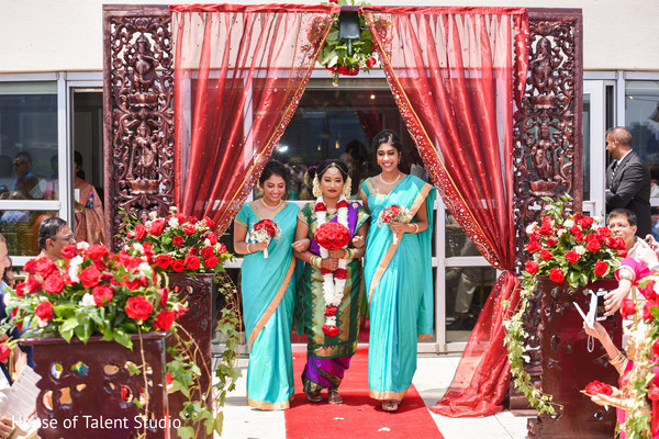 Indian bride making her entrance to ceremony with bridesmaids.