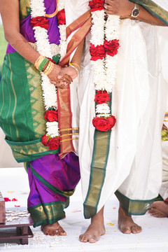 Indian bride and groom holding hands at ceremony.