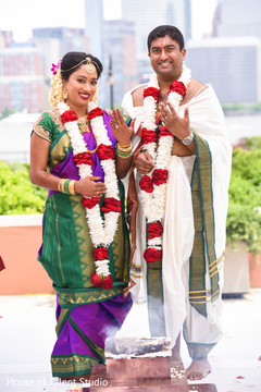 Joyful Indian couple showing their wedding rings.