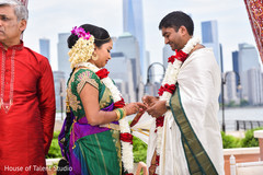 Indian bride putting ring to groom capture.