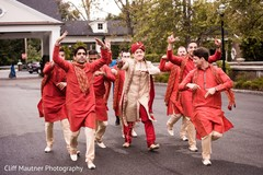 Indian groom with groomsmen at baraat capture.