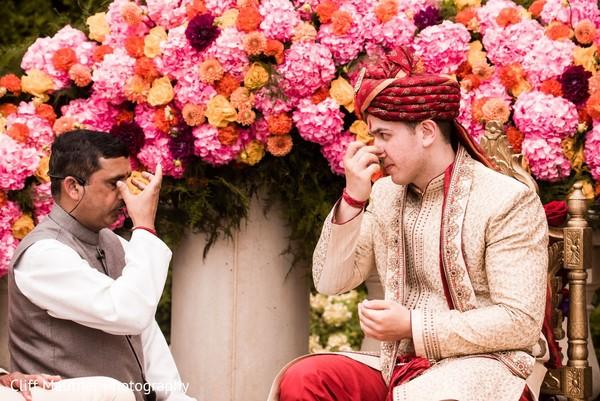 Indian groom at mandap during pre-wedding rituals.