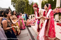 Indian groom negotiating with bridesmaids.