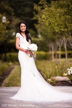 Stunning Indian bride posing on her white wedding dress.