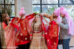 Indian bride being assisted by family