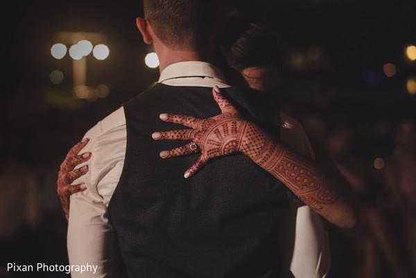 Indian bride hugging groom.