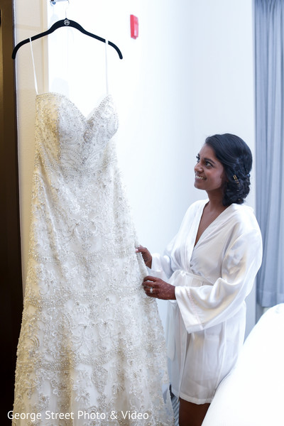 Indian bride admiring her white wedding dress