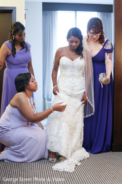 Indian bridesmaids helping maharani getting ready
