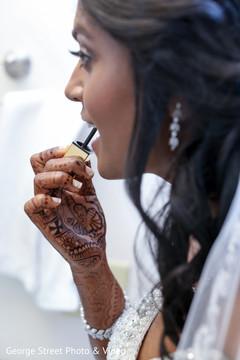 Indian bride putting lipstick on
