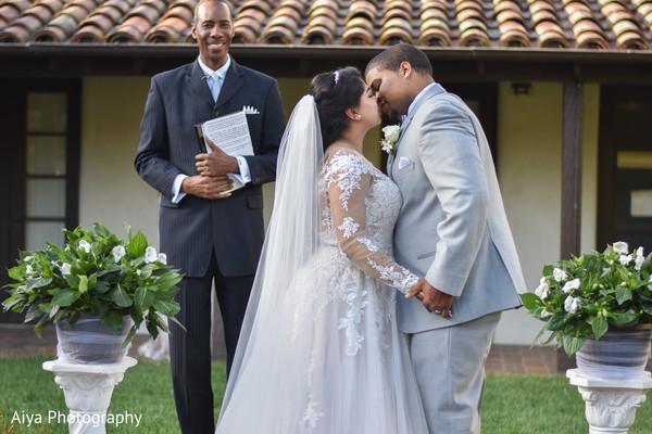 Indian groom kissing bride.