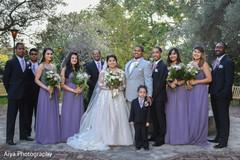 Maharani and rajah posing with bridesmaids and groomsmen.