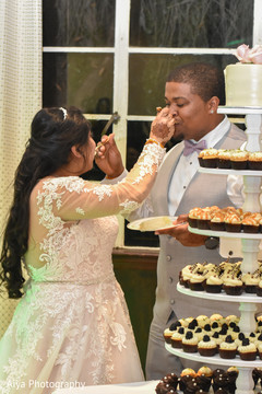 Sweet Indian couple cutting their wedding cake.