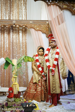 Indian groom guiding  bride on seven steps ritual.