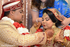 Indian bride getting blessed chain from groom.