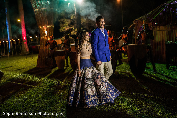 Lovely Indian couple walking hand in hand to sangeet party.