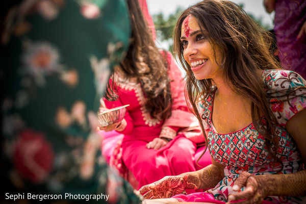 Indian bride with turmeric paste all over her face.