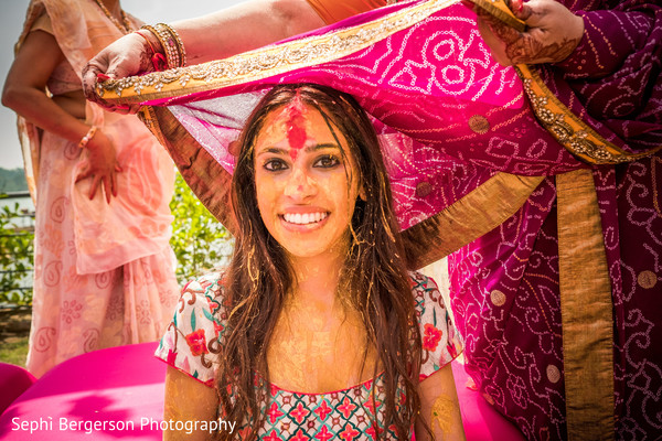Indian bride being covered with ghoonghat at haldi ritual.