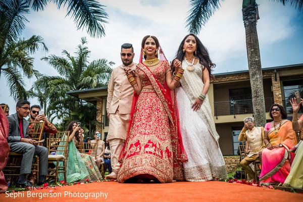 Joyful Indian bride making her entrance to ceremony.