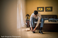 Indian groom putting his shoes on.