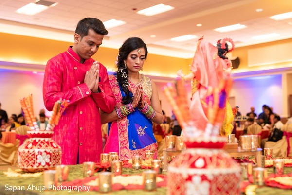 Indian bride and groom making prayers to their gods at sangeet.