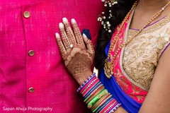 Closeup capture of Indian bride mehndi art and engagement ring.