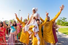 Indian groomsmen lifting up the groom at baraat celebration.