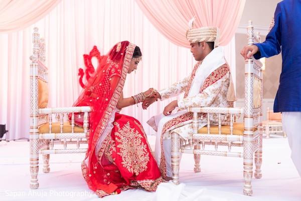 Indian bride putting bracelet to groom.