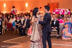 Indian bride and groom dancing at reception.