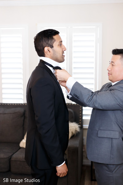 Indian groom being helped to get ready.