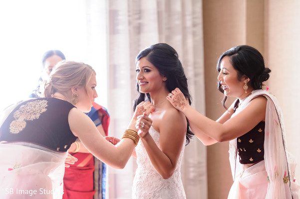 Indian bridesmaids helping bride to put her jewelry.