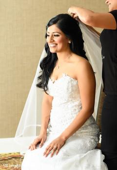 Enchanting Indian bride putting her white veil.