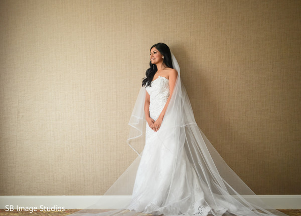 Glamorous indian bride posing with her white wedding dress.