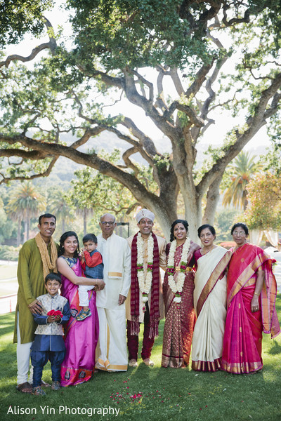 Indian bride and groom posing with guests