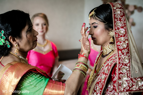Indian bride getting the forehead dot .