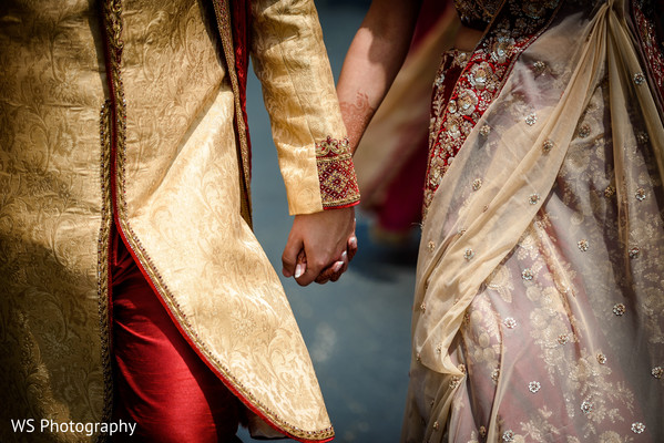 Closeup capture of Indian bride and groom holding hands.