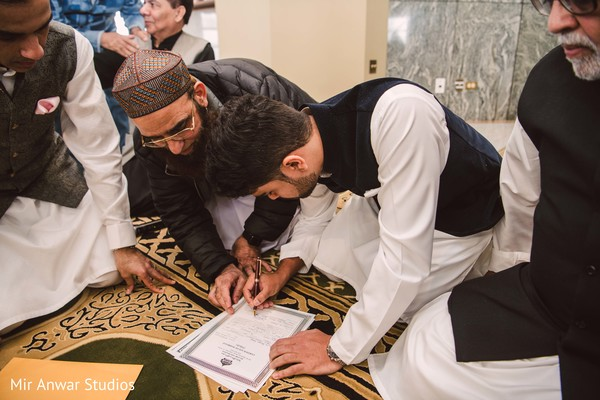 Indian groom signing his wedding certificate.