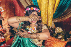 Indian bride posing with her mehndi art on hands.