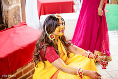 Indian bride smeared with yellow turmeric paste.