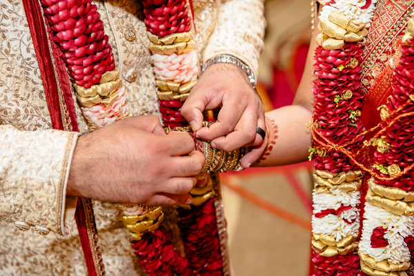 Indian groom putting ceremonial red thread on maharani's wrist.