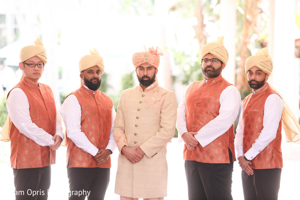 Indian groom posing with his groomsmen outdoors.