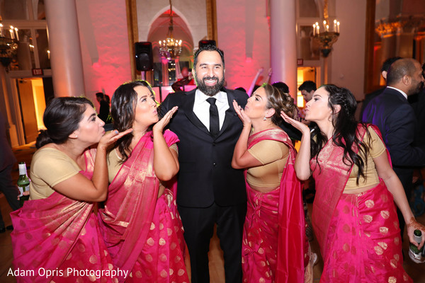 Indian groom posing with bridesmaids.