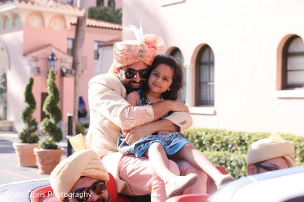 Joyful Indian groom hugging flower girl.