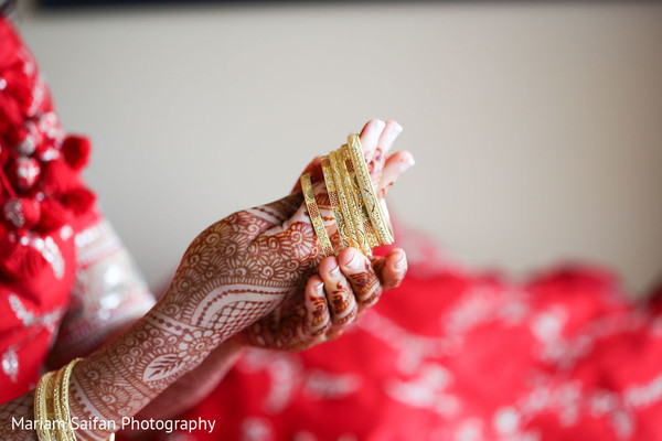 Indian bride putting her bangles on.