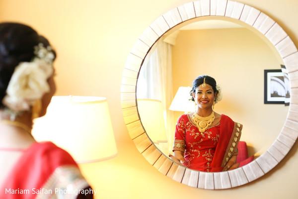 Enchanting Indian bride looking in mirror.
